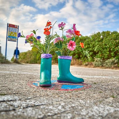 Blaue Gummistiefel mit Blumen bepflanzt stehen auf einem Weg zum Strand