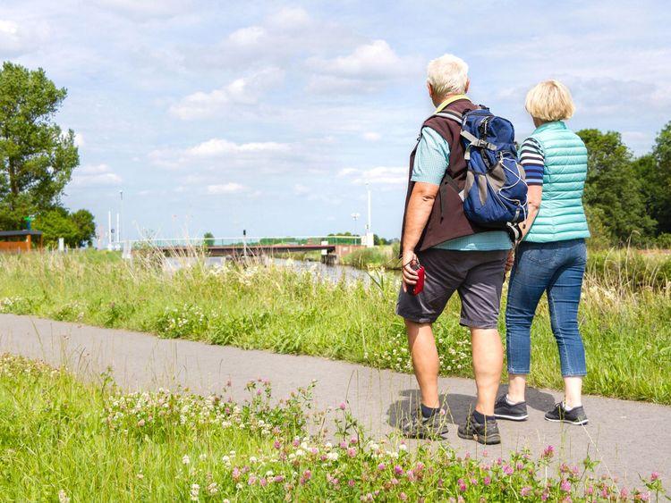 Ein Paar wandert entlang des Ems Jade Kanals und blickt auf eine Brücke