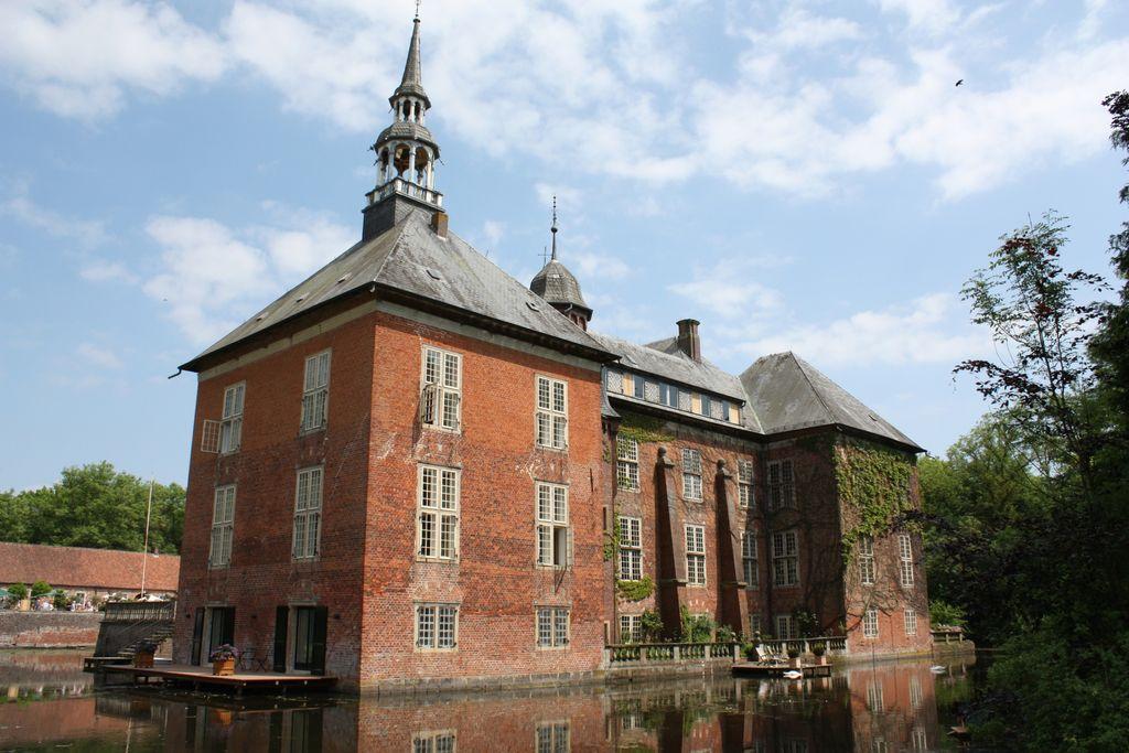 Außenaufnahme vom Schloss Gödens, umgeben von Wasser