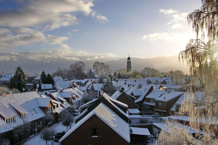 Luftaufnahme über die beschneiten Dächer der Stadt Leer im Winter