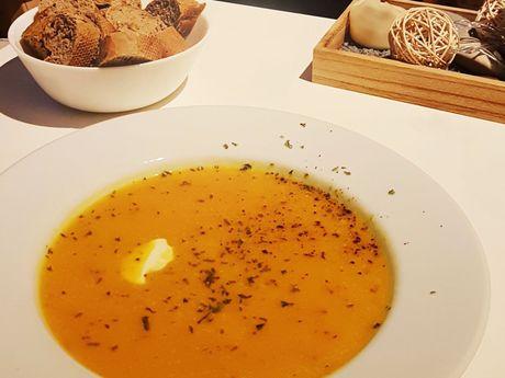 Ein Teller mit Kürbissuppe, im Hintergrund steht eine Schale mit Brot
