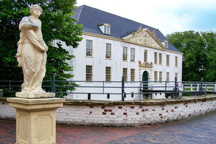 Außenansicht auf das Schloss Dornum mit Statue im Vordergrund