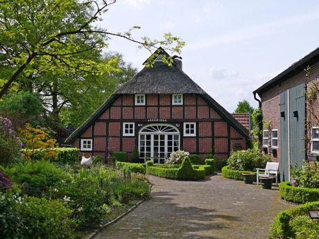 Bauernhaus in Wiefelstede mit Garten im Vordergrund
