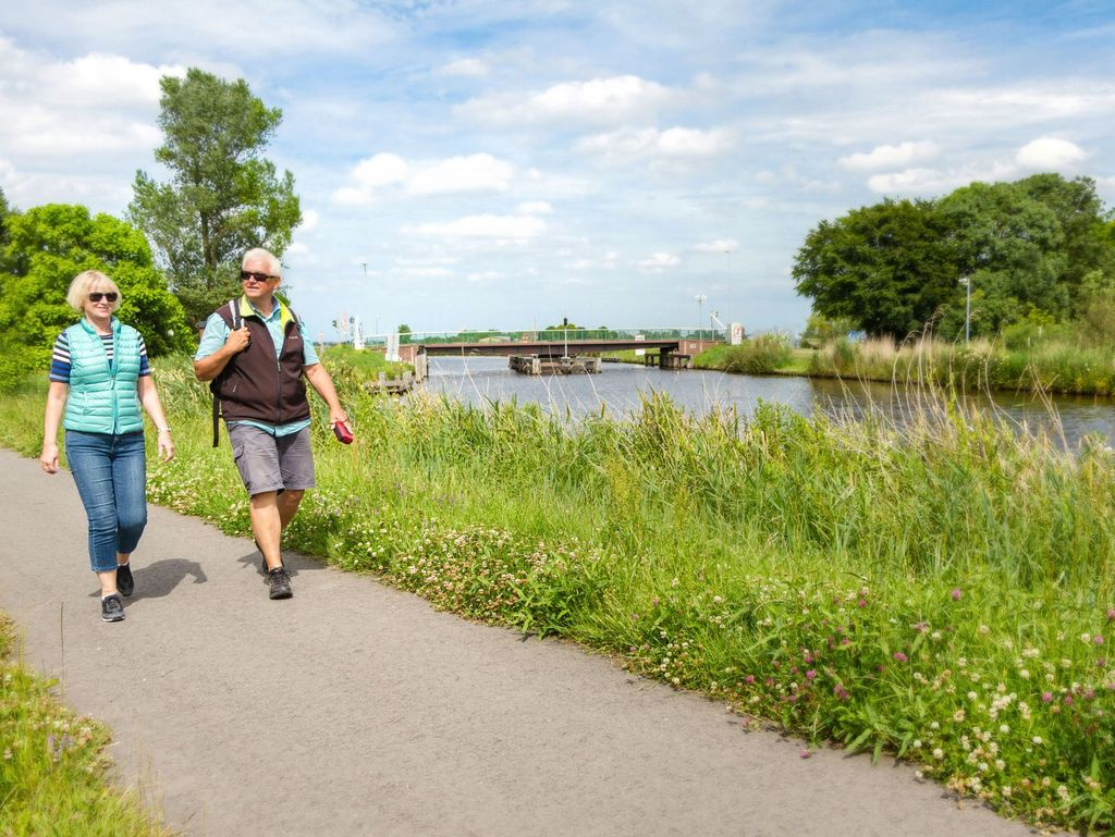 Ein paar wandert entlang des grün bewachsenen Ems-Jade-Kanals