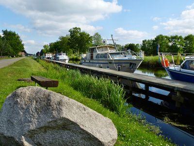 Blick vom Wegesrand auf die Boote auf dem Kanal in Ostrhauderfehn
