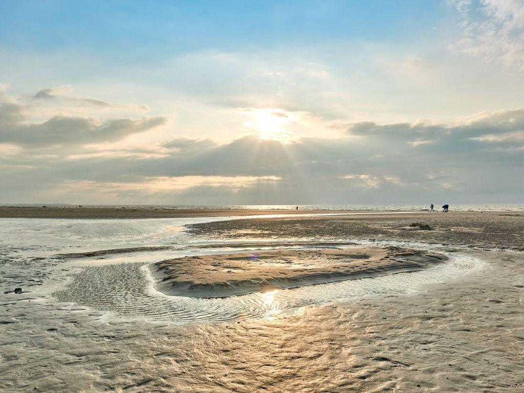 Auf einer Wattwanderung in Ostfriesland mit Blick auf die Sonne über dem Watt
