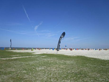 Strandkörbe und Fahnen am Strand in Dornum