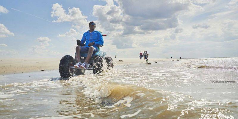 Mann fährt mit dem Wattmobil über den Strand von Langeoog
