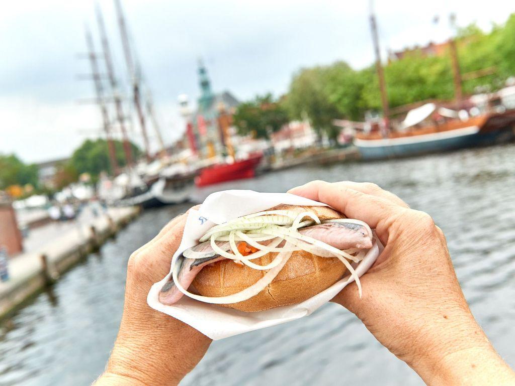 Eine Person hält ein Matjesbrötchen am Hafen von Emden