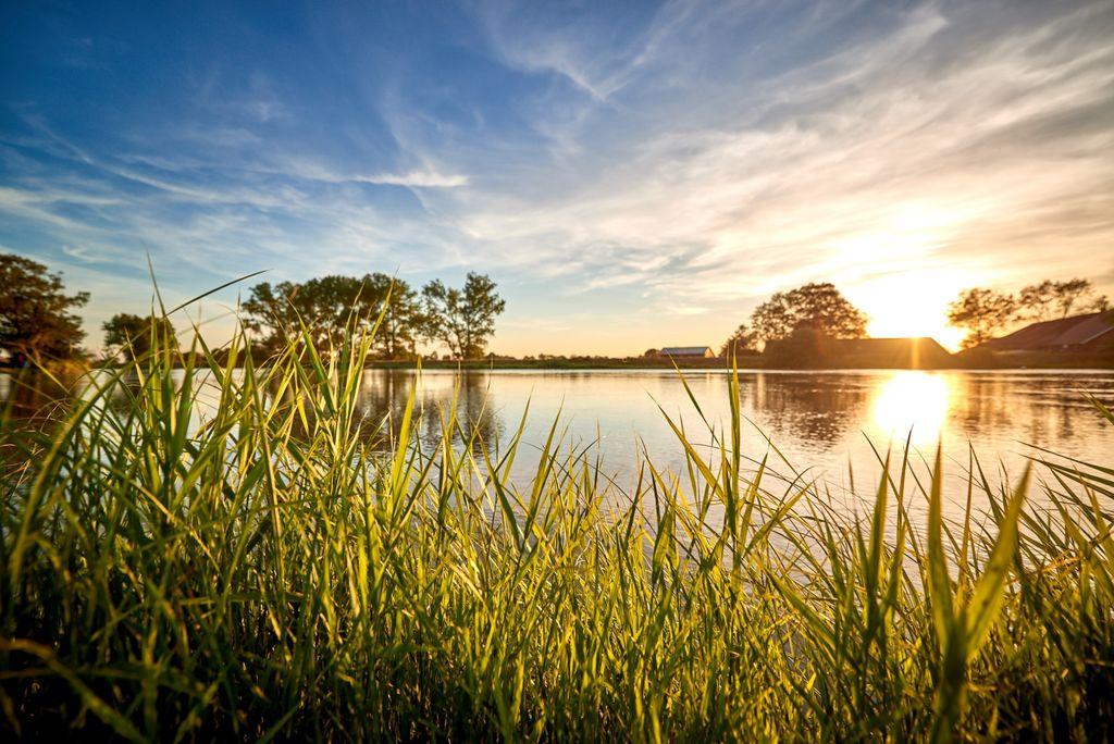 Goldener Sonnenuntergang mit Spiegelung im Wasser der Jümme