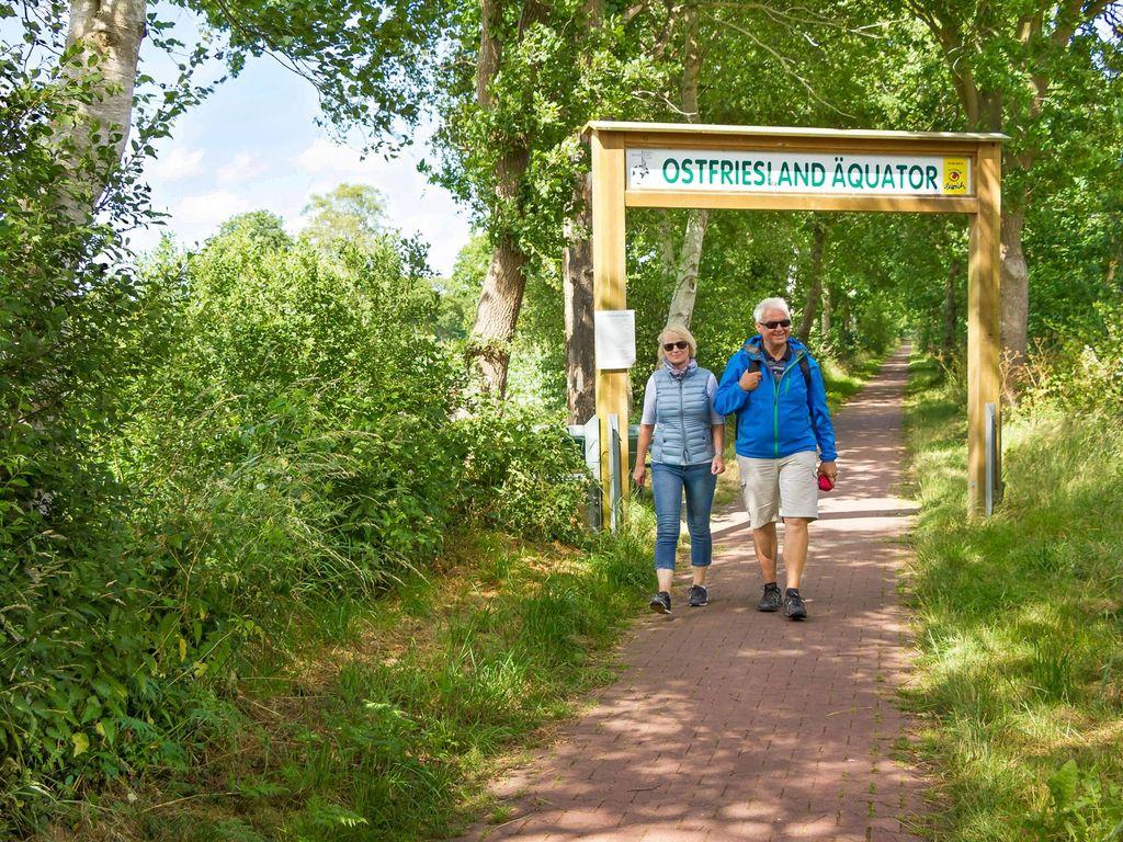 Ein Paar wandert entlang des Ostfriesland Äquators bei Sonnenschein