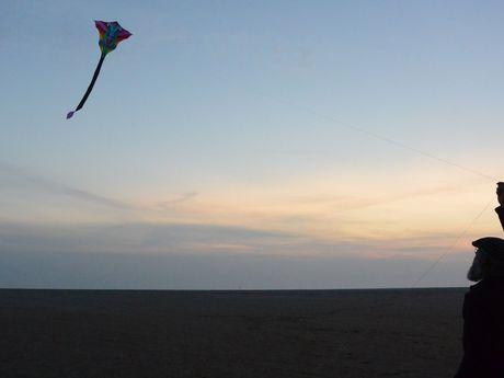 Ein Mann lässt einen Drachen steigen bei Sonnenuntergang