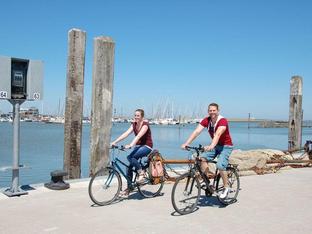 Radfahren am Hafen in Norddeich mit der Nordsee im Hintergrund
