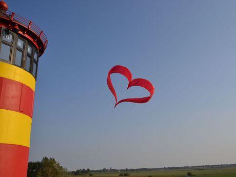 Herzförmiger roter Drache am wolkenlosen Himmel beim Pilsumer Leuchtturm