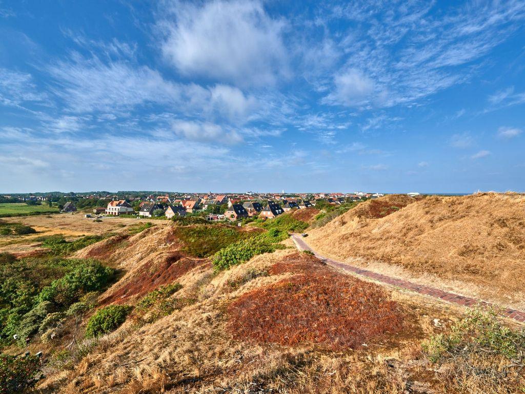 Blauer Himmel über Dünen und Häusern des Inselkerns auf Langeoog