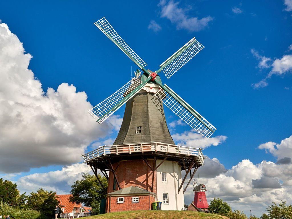 Blauer Himmel, Wolken und Sonnenschein über den Zwillingsmühlen von Greetsiel