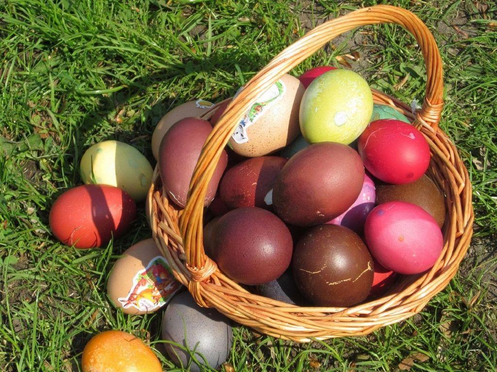 Ein Weidenkörbchen voller bunte gefärbter Ostereier