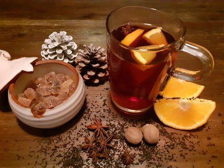 Ein Glas mit Teepunsch, braunem Kandiszucker, Zitrone und Gewürzen