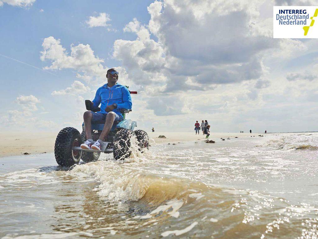 Ein Mann mit einem speziellen Rollstuhl am Meer von Langeoog