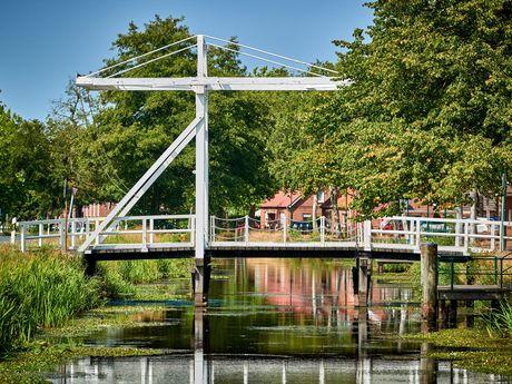 Weisse Klappbrücke über Kanal in Großefehn