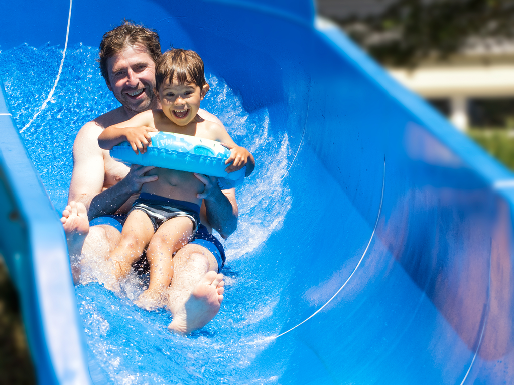 Ein Mann und ein Kind rutschen eine Wasserrutsche hinunter