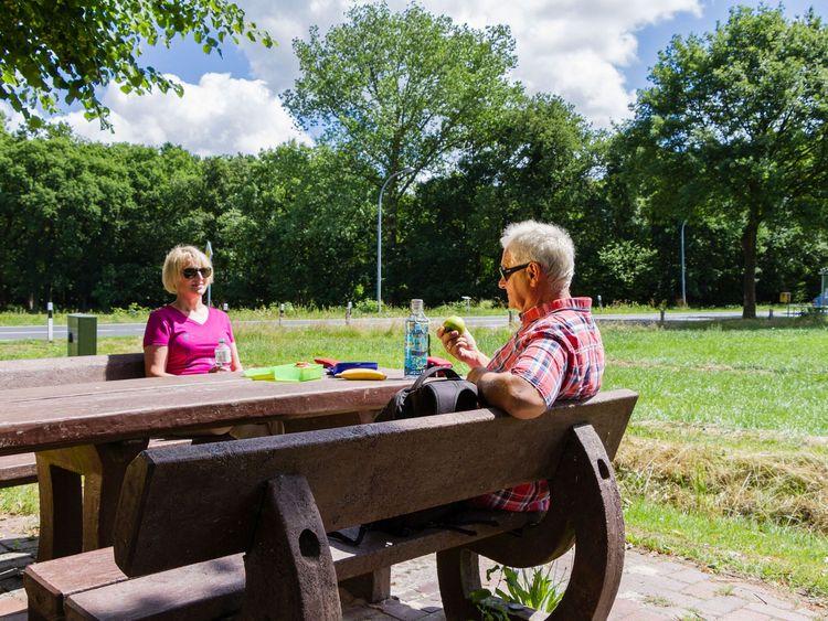 Ein Paar macht Rast auf einer Bank während einer Wanderung in Ostfriesland