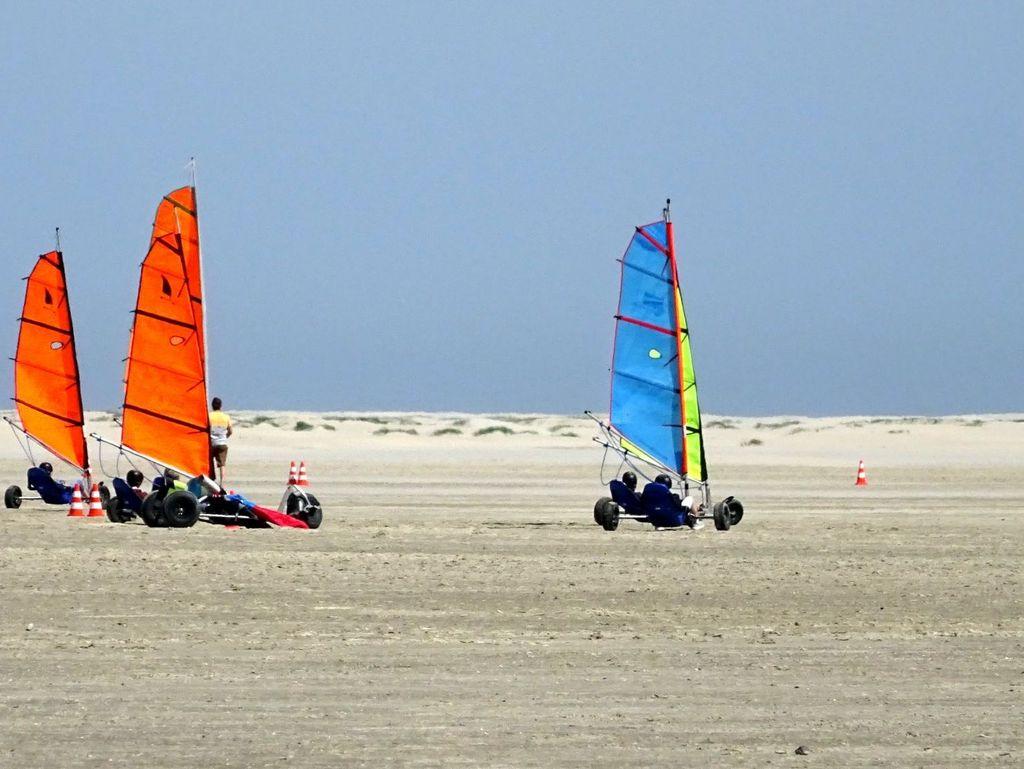 Bunte Kitebuggys fahren am Strand von Borkum