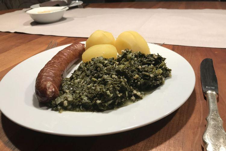 Ein Teller mit Grünkohl, Kartoffeln und Pinkelwurst