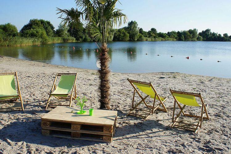 Stühle und Palme am Strand der Kieselbucht in Großheide