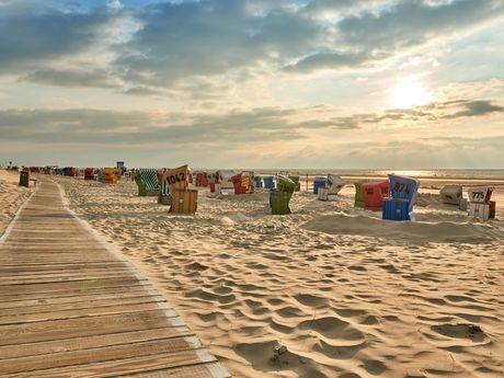 Sonnenuntergang über bunten Strandkörben im Sand auf Langeoog
