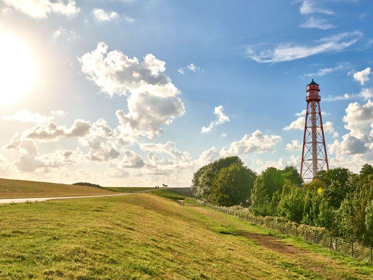 Sonnenschein und blauer Himmel über dem Deich am Campener Leuchtturm