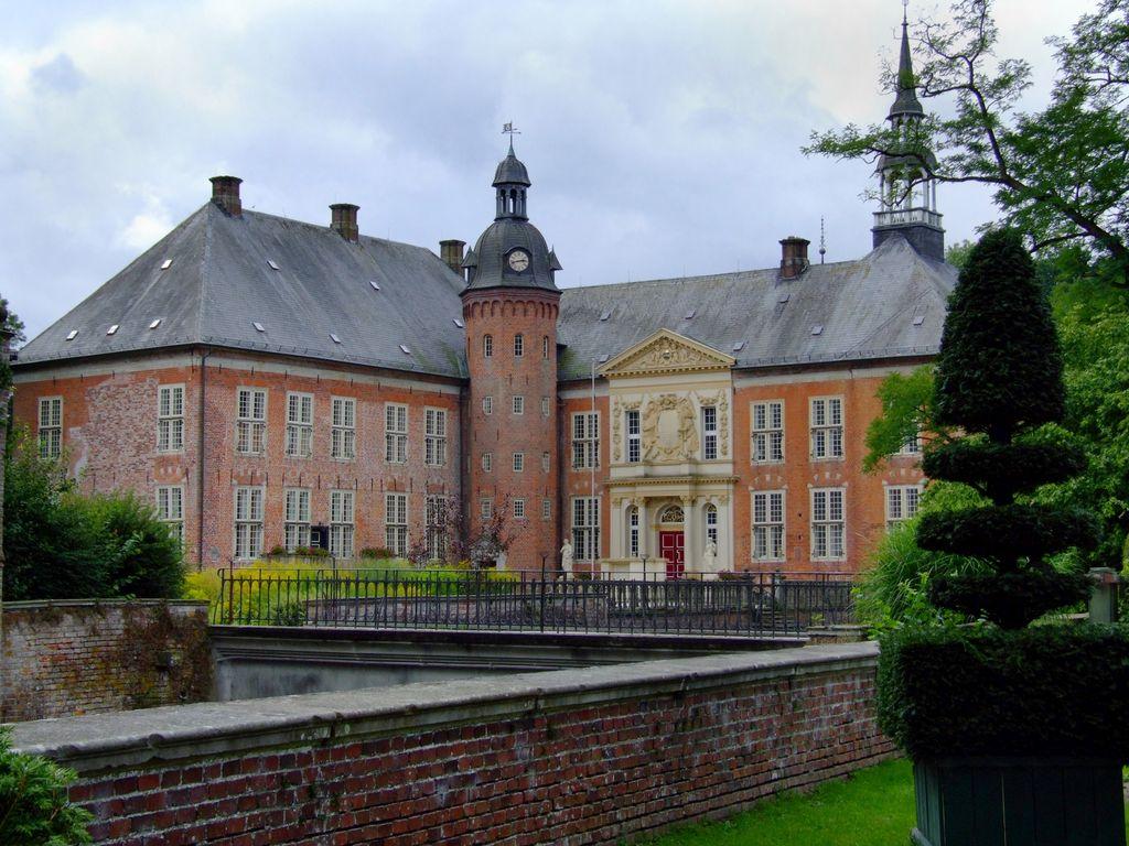 Blick auf den mit Ornamenten verzierten Eingang des Schloss Gödens aus dem Schlosspark