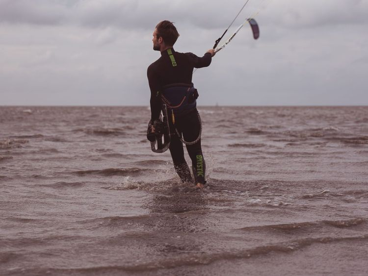 Ein Kitesurfer in den Wellen vor dem Wangerland