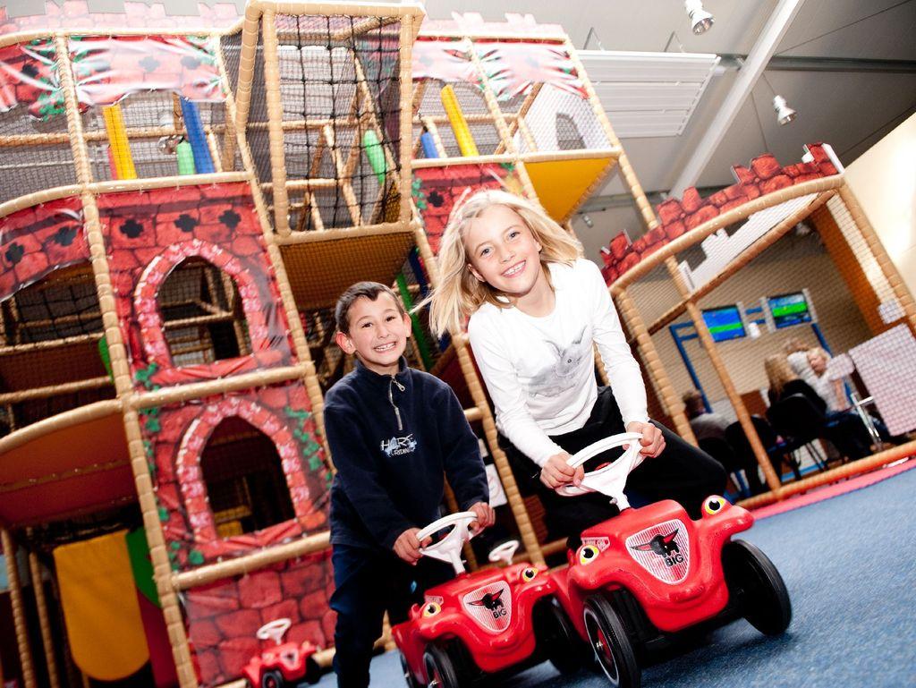 Zwei Kinder beim Spielen im Spielpark, im Hindergrund ist ein großer Spielturm zu sehen