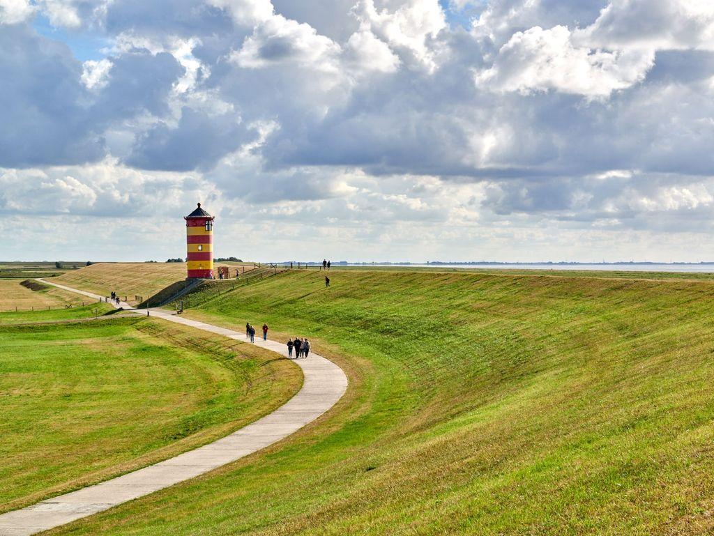 Menschen laufen auf dem Weg zum Pilsumer Leuchtturm