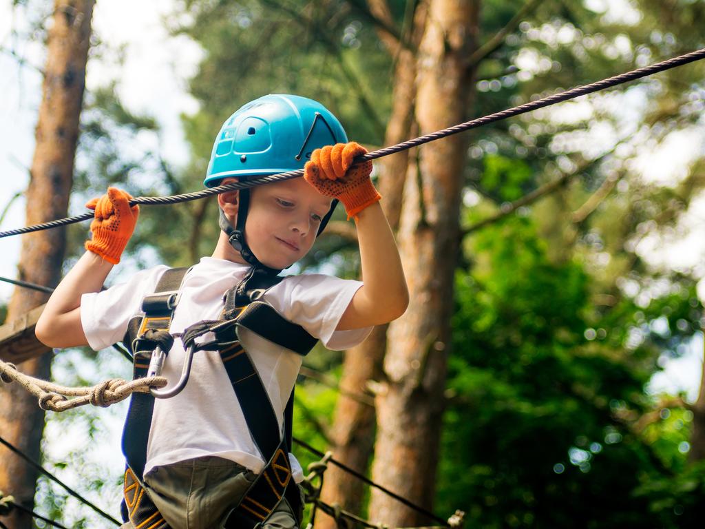 Junge mit Kletterausrüstung hangelt sich von Baum zu Baum
