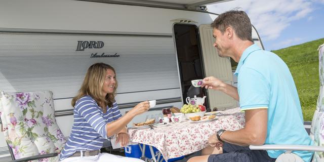Ein Paar an einem gedecktem Tisch vor einem Wohnwagen