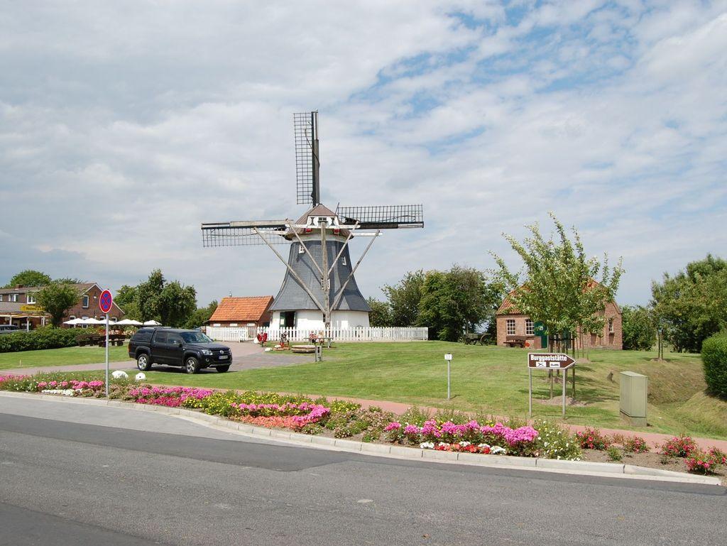 Mühle in Werdum mit Rasenfläche und Blumen im Vordergrund