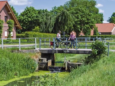 Zwei Fahrradfahrer auf einer Brücke über einem Kanal bei Jheringsfehn