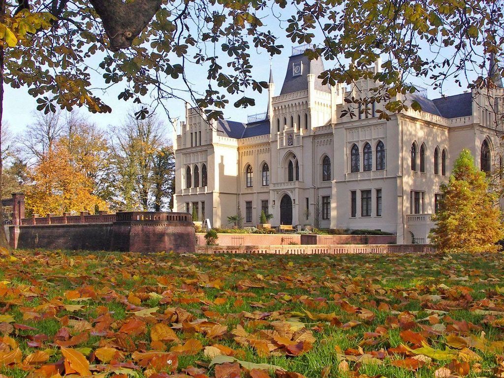 Herbstliches Laub auf dem Boden und an den Bäumen bei der Evenburg in Leer