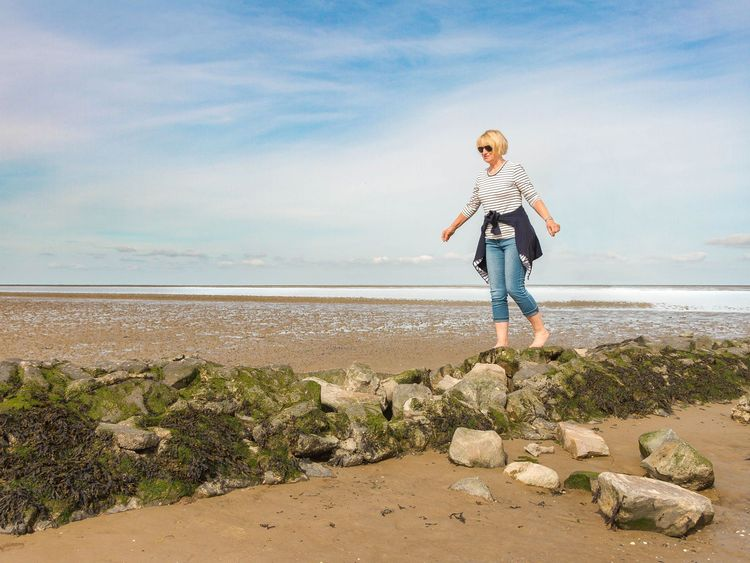 Eine Frau läuft auf Steinen im Wattenmeer während einer Wanderung