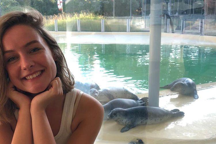Sylie Gühmann in der Seehundstation Norden mit Seehunden im Hintergrund