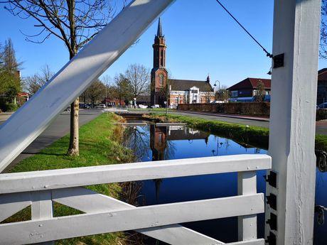 Blick durch das Holz einer weißen Fehnbrücke auf die Kirche von Rhauderfehn