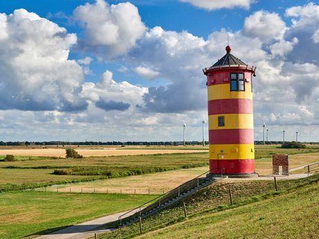 Blick auf den Pilsumer Leuchtturm mit Landschaft im Hintergrund