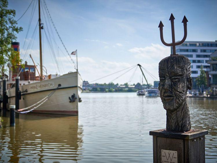 Hölzerne Statue im Hafenbecken von Leer, das Schiff Prinz Heinrich im Hintergrund