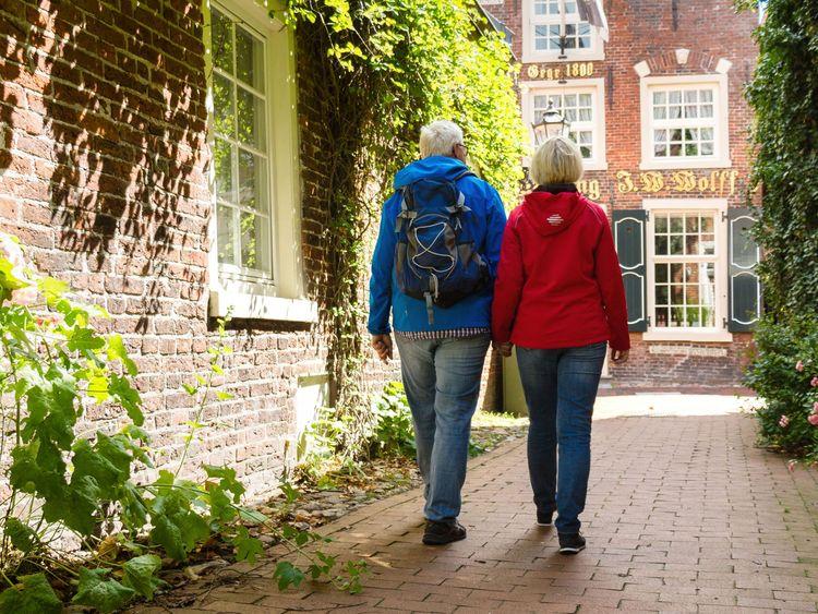 Ein Paar wandert durch die Altstadt von Leer bei Sonnenschein