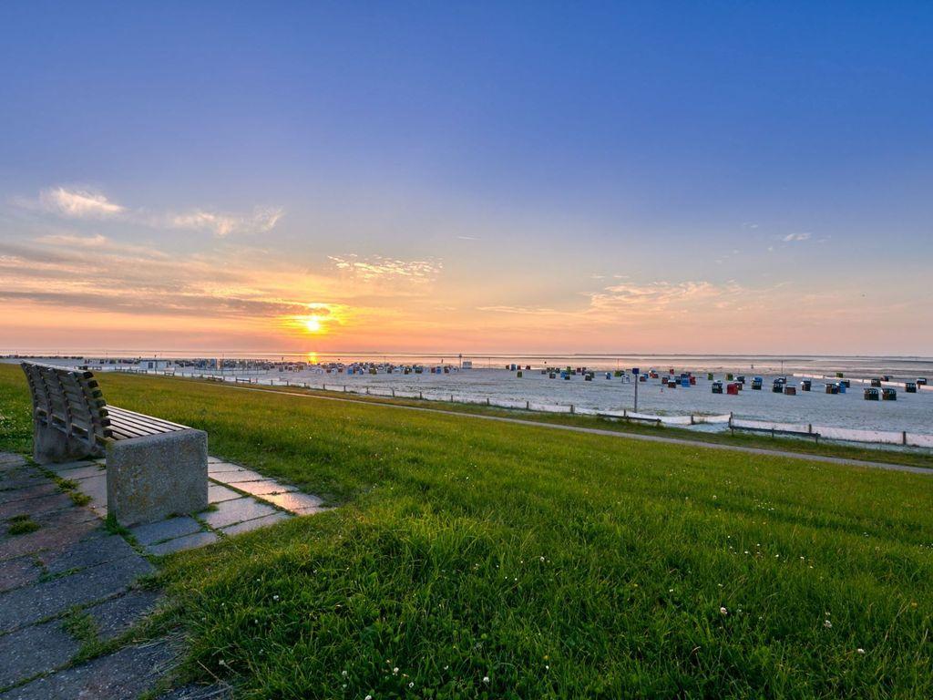 Eine Bank auf dem Deich bei Neuharlingersiel mit Blick auf den Sonnenuntergang über dem Strand