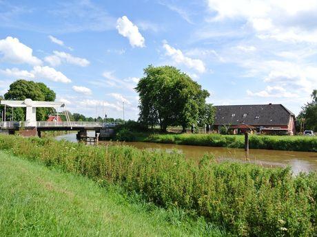 Weiße Ziehbrücke über dem Wasser bei Stickhausen
