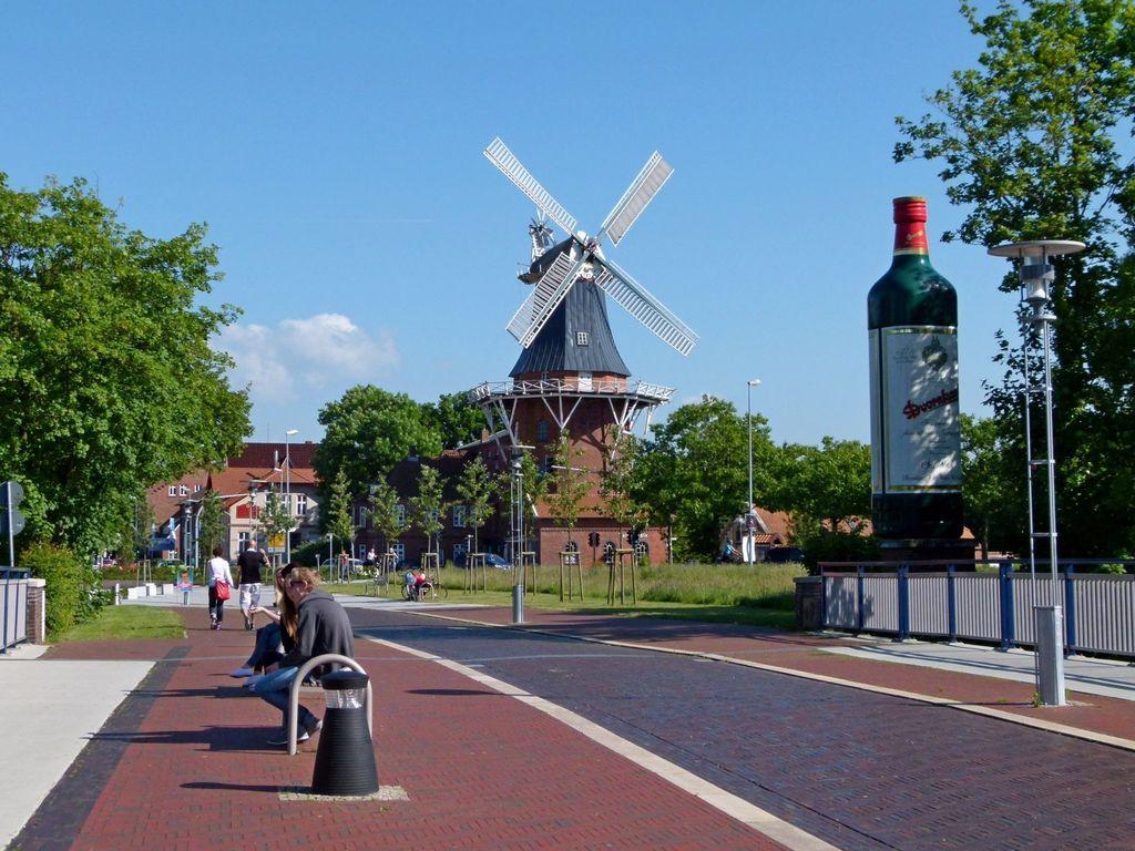 """Blick auf die Mühle von Norden mit großer Statue von einer """"Dornkaat"""" Flasche im Vordergrund"""