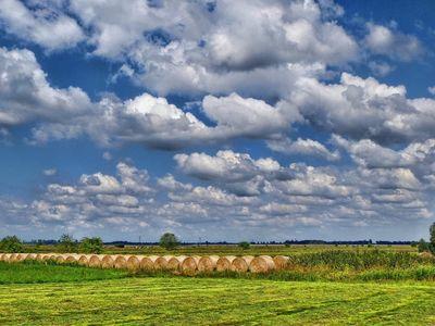 Blauer Himmel voller Wolken über einer langen Reihe Strohballen auf einem Feld in Tergast bei Neermoor